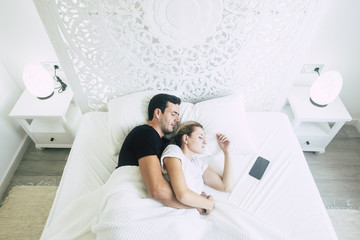 Above view of couple of beautiful young people male and female sleep together in the bedroom on the bed. White bright room and window morning light. Phone near them with alarm to wake up