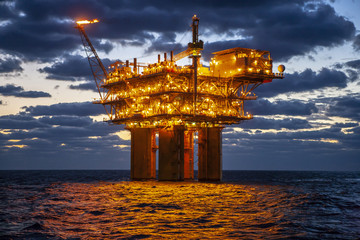 Illuminated oil exploration platform in sea against cloudy sky during sunset