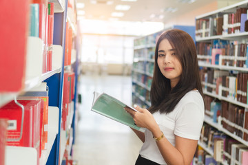 Young asian female college looking to camera while reading textbook in library.