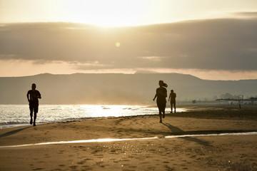 couple running on the beach at sunset