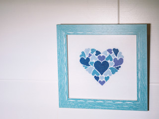 Picture frame with blue sewing heart on white wall