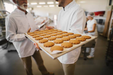 Close up of fresh cookies on big tray in food factory. Blurred picture of two male employees in sterile clothes talking in background.One man is holding tray.