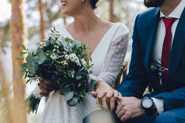Close up of bride holding bridal bouquet during ceremony