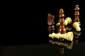 Chess pieces on a black background. Play chess. Checkmate. The concept of defeat and victory.
