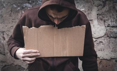 Homeless man holding blank cardboard.