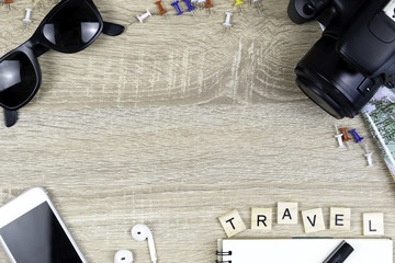 Top view of travel stuff with center copy space on wooden background, Mobile Phone, camera, world map, glasses and book etc. Flat lay for travel kit. Travel planning concept