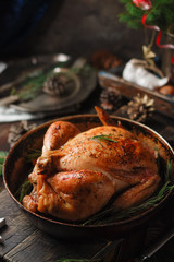 Homemade Fresh Christmas roasted chicken with tangerines on a rustic wooden background. Close up