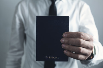 Caucasian businessman holding passport.