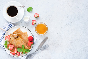 French crepes or blini with strawberries, honey and cup of coffee on table. Top view and copy space for text, recipe or restaurant cafe menu