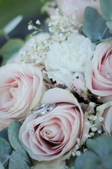 wedding rings on a bouquet of white roses