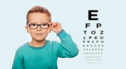 Little boy adjusting his new eyeglasses, on the eye chart background. Vision correction for children