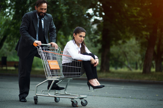 Beautiful businesswoman sitting in shopping cart. Feels in despair. Her male partner standing behind.