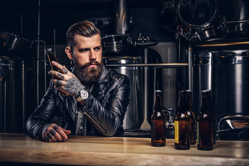 Stylish bearded biker dressed black leather jacket sitting at bar counter in indie brewery.