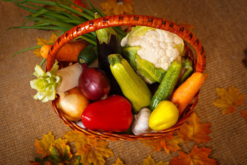 Basket with a mix of vegetables. Autumn harvest of vegetables on a background of yellow leaves