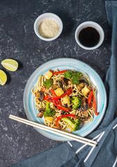 Asian tofu soba noodle bowl on stone background.