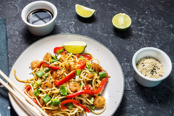 Stir fry noodles with vegetables and shrimps on stone background.
