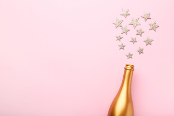 Decorated champagne bottle with stars on pink background