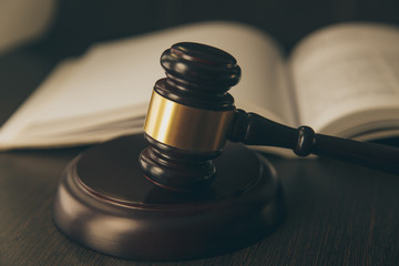 Law concept - Open law book with a wooden judges gavel on table in a courtroom or law enforcement office on blue background. Copy space for text