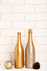 Champagne bottle with christmas bauble and cone on brick wall background