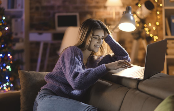Smiling woman connecting with her laptop on Christmas Eve