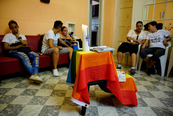 A rainbow flag decorates an improvised altar as activists supporting the lesbian, gay, bisexual and transgender community (LGBT) chat prior to a religious service in Havana
