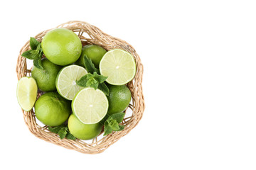 Ripe limes in basket isolated on white background