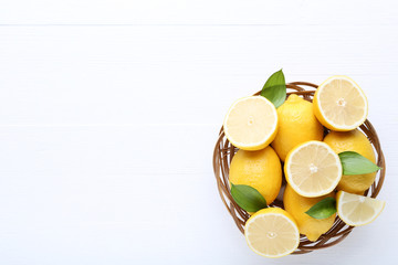 Ripe lemons in basket on white wooden table