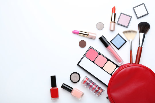 Different makeup cosmetics with brushes on white background