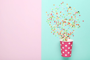 Pink paper cup with confetti on colorful background
