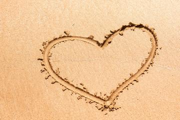 Heart symbol written on the wet sea sand