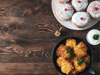 Jewish holiday Hanukkah concept and background. Hanukkah food doughnuts and potatoes pancakes latkes, oil and traditional spinnig dreidl on wooden table. Top view or flat lay. Copy space for text.