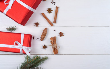 Christmas background with red gift boxes, fir tree branches, pine cones, cinnamon sticks and stars anise on white wooden background, free space. Holiday greeting card, copy space. Flat lay, top view