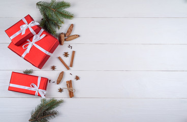 Christmas background with red gift boxes, fir branches, pine cones, cinnamon sticks and stars anise, free space. Red Christmas gift boxes on white wooden background, copy space. Flat lay, top view