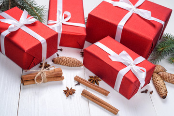 Christmas background with red gift boxes, fir tree branches, pine cones, cinnamon sticks and stars anise. Red Christmas gift boxes on white wooden background. Holiday greeting card