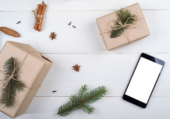 Mobile smart phone with blank white screen for app presentation with Christmas decorations, copy space. Christmas gifts on wooden background. Flat lay, top view. Application mock up template