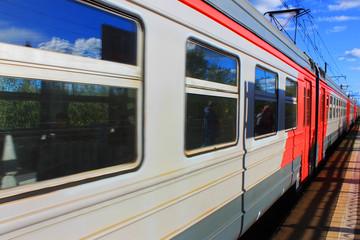 Local Train in Motion at Platform on Railway Station. Train Arriving at the Station on Summer Day. View of Old Grey and Red Train with Doors Closed and Sky Reflecting on the Windows