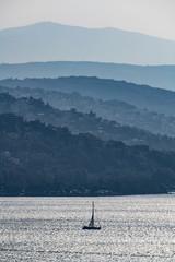Barca in controluce al tramonto, con montagne a profili sfumati con luci cangianti, tra nebbie e freddo