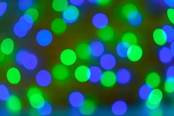 Christmas bokeh background, copy space. Defocused new year bokeh lights, free space. Blurred blue and green bokeh. Abstract holiday glitter background