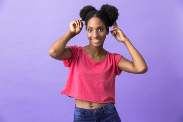Photo of beautiful african american woman smiling and touching her afro buns, isolated over violet background