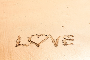 "Word ""love"" written on the wet sea sand"