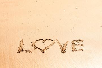 """Word """"love"""" written on the wet sea sand"""