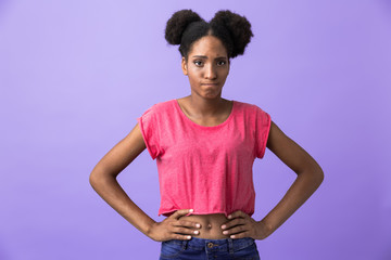 Photo of upset african american woman standing with hands on waist, isolated over violet background