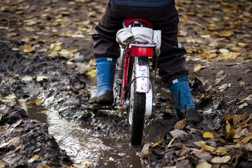 child rides a bike through a mud puddle in the mud in a forest in autumn