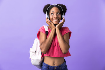 Photo of amusing african american woman wearing backpack and white headphones listening to music, isolated over violet background