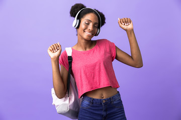 Photo of attractive african american woman wearing backpack and white headphones dancing, isolated over violet background