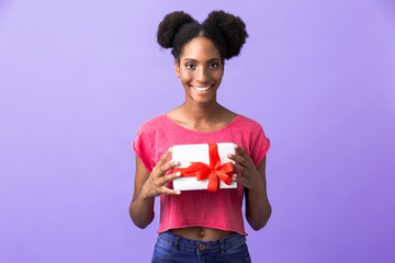 Photo of cute african american woman smiling and holding present box with red bow, isolated over violet background