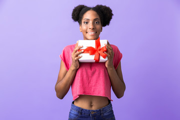 Photo of positive african american woman smiling and holding gift box with red bow, isolated over violet background