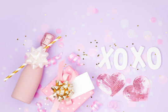 Mini bottles of champagne with confetti, tinsel and paper decoration. Valentines day or birthday party concept theme. Flat lay, top view