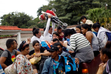 A Honduran migrant, part of a caravan trying to reach the U.S., holds a baby carriage  in Quezaltepeque
