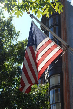 An American flag hanging outside of a downtown building